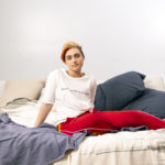 A transmasculine gender-nonconforming person sitting on a bed.